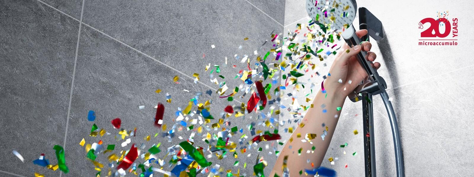 una mano tieni il soffione della doccia mentre escono coriandoli di festa